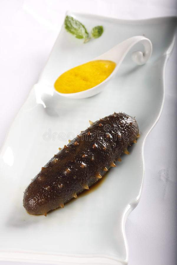 Cooked sea cucumber. On white plate with yellow sauce royalty free stock photo