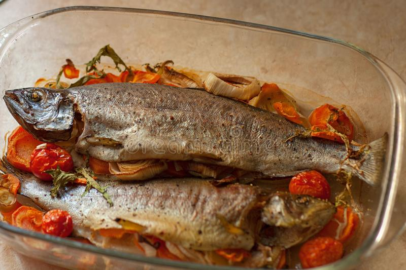 Cooked sea fish dorado in a glass saucepan with lemon and spices and vegetables. Homemade recipe cooking concept. Flat top view from above stock photography
