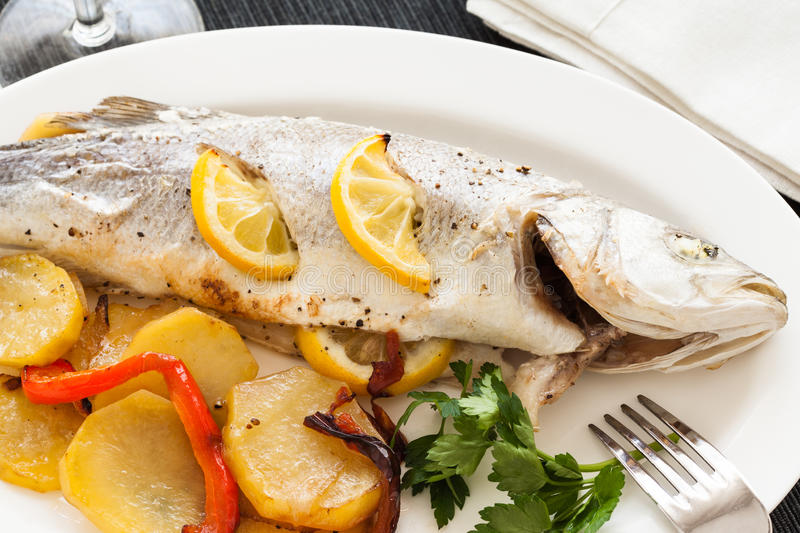 Cooked seabass. With lemon, potatoes and peper in a plate, ready to eat royalty free stock photos