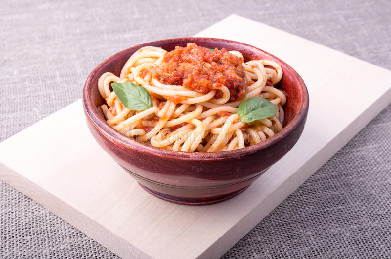 Cooked spaghetti closeup on a wooden stand. Cooked spaghetti with tomato relish and basil leaves in a brown small wooden bowl closeup on a wooden stand stock image