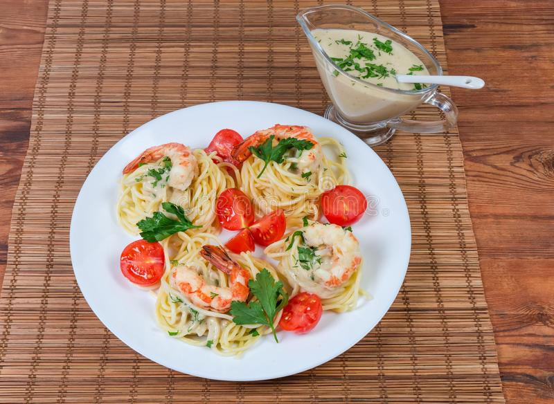 Cooked Spaghetti with shrims and tomatoes, sauce in sauce boat. Cooked and twisted Spaghetti pasta with king prawn tails, cherry tomatoes on dish, sauce in sauce stock photo