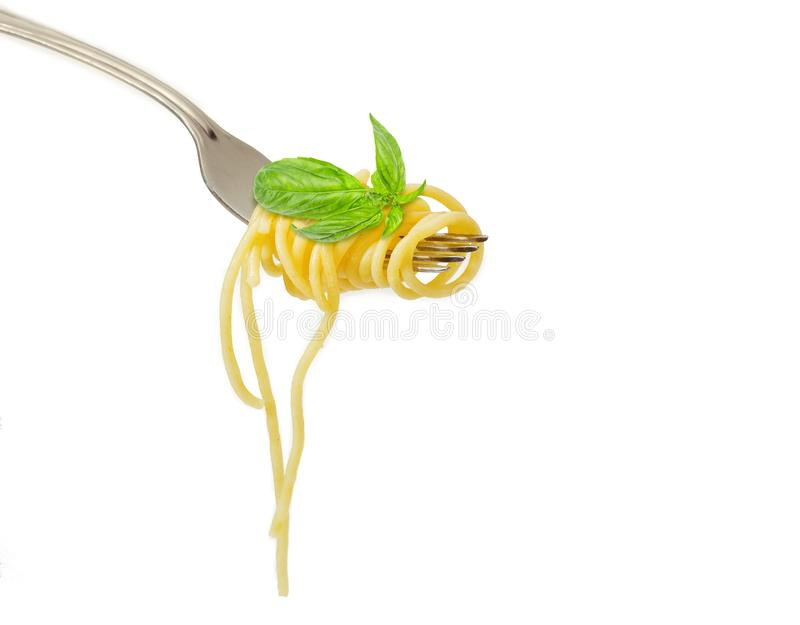 Cooked spaghetti twisted around fork and basil liaves. Fragment of the stainless steel fork with cooked long thin pasta twisted around and small basil sprig stock photo