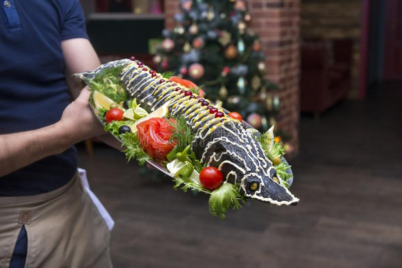 Cooked sturgeon on a tray in the hands of a waiter, fish dish royalty free stock images