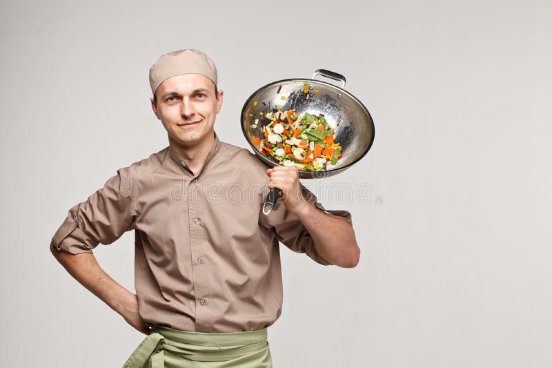 Cooker chef tosses vegetables in pan am smile stock images