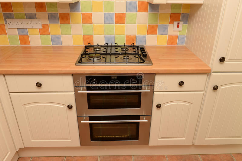 Cooker in a modern kitchen. With a tiled wall royalty free stock photo