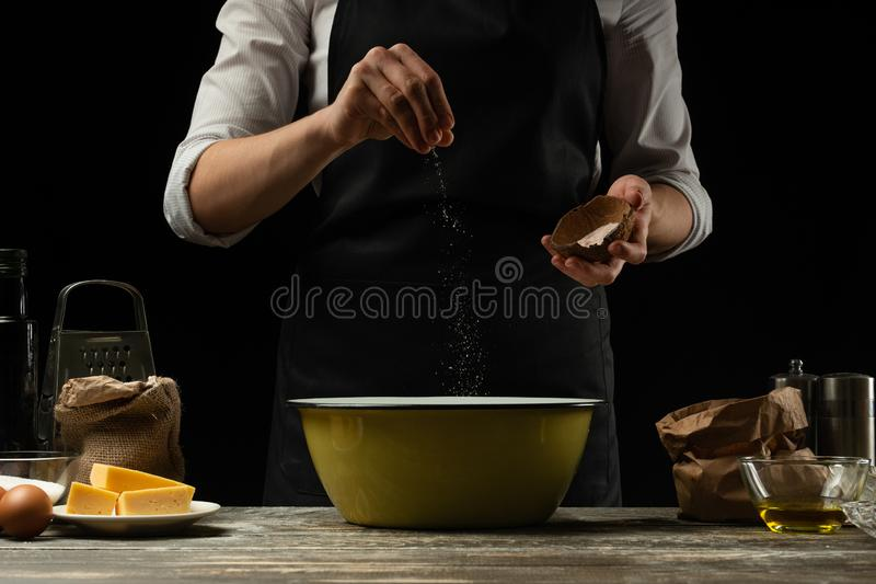 Cookery. The cook cooks dough for pasta, pizza, bread. Sprinkles with salt. Delicious food, recipes, cooking, gastronomy,. Background for design on a black stock image