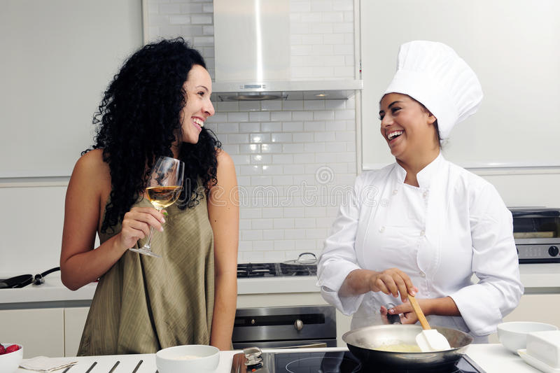 Cookery course: laughing. Cookery course in a modern: chef and young woman cooking risotto and laughing stock image