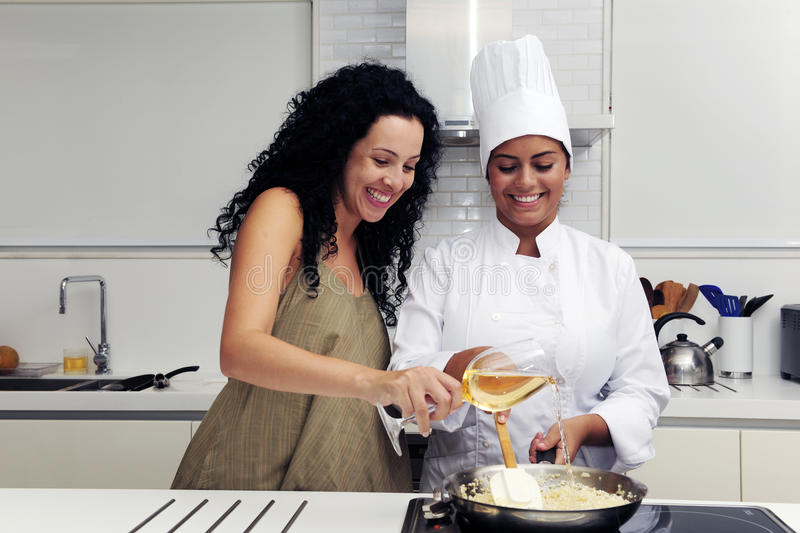 Cookery course: pouring wine into pan. Cookery course: pouring wine into a pan with risotto stock image