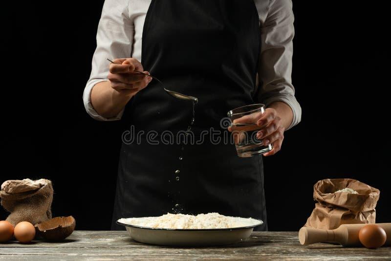 cookery De kok kookt deeg voor deegwaren, pizza, brood Giet water in de bloem Heerlijk voedsel, recepten, het koken, gastronomie, stock foto