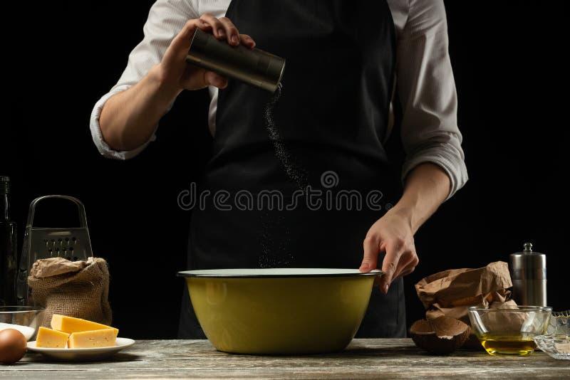cookery Kucharz gotuje ciasto dla makaronu, pizza, chleb Kropi z solą Wyśmienicie jedzenie, przepisy, kucharstwo, gastronomy, obraz stock