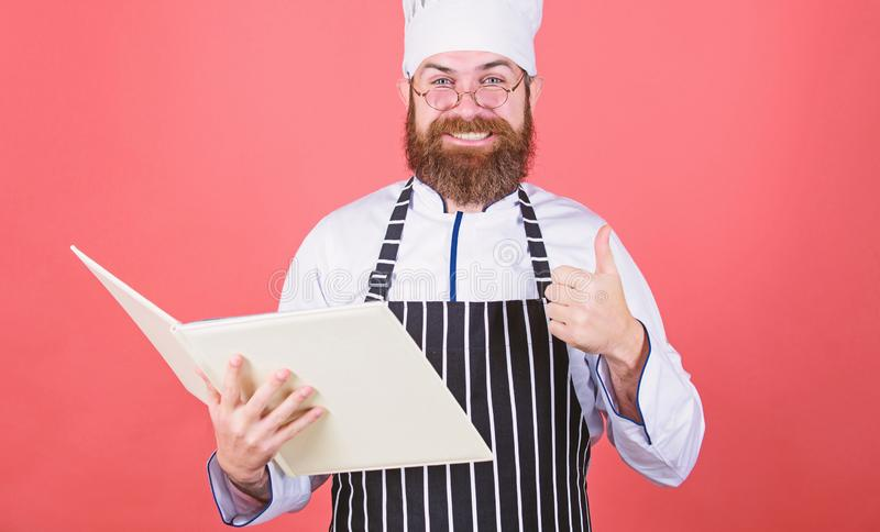 Cookery on my mind. Improve cooking skill. Book recipes. According to recipe. Man bearded chef cooking food. Culinary. Arts concept. Amateur cook read book royalty free stock images