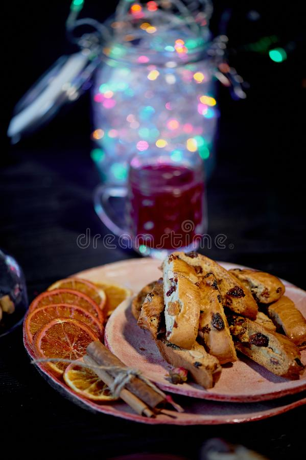 Cookie biscotti on a dark background. A glass of red wine or mulled wine.Christmas garland stock photo
