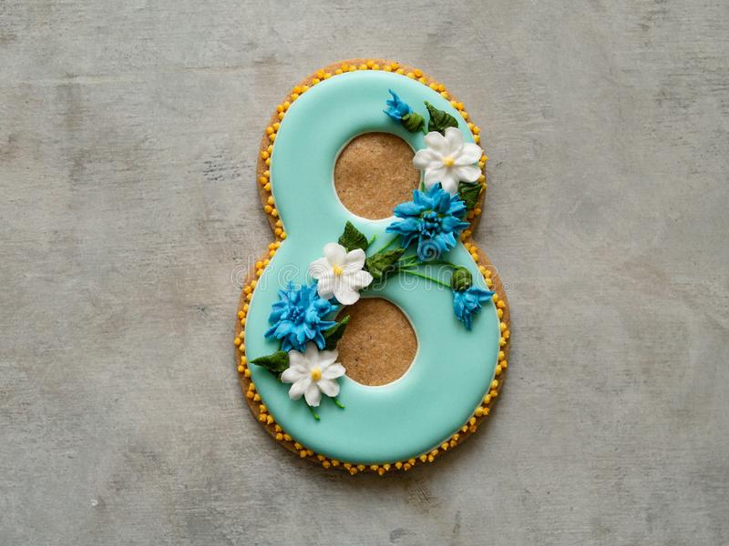 Cookie covered with blue glaze made in a form of number eight with flowers - cornflowers and daisies - on gray background. Ginger stock photos