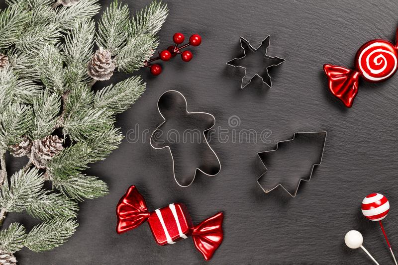 Cookie cutters for Christmas baking with red decorative sweets and lollipops with snowy fir branches with cones on slate. flat lay. Cookie cutters for Christmas royalty free stock image