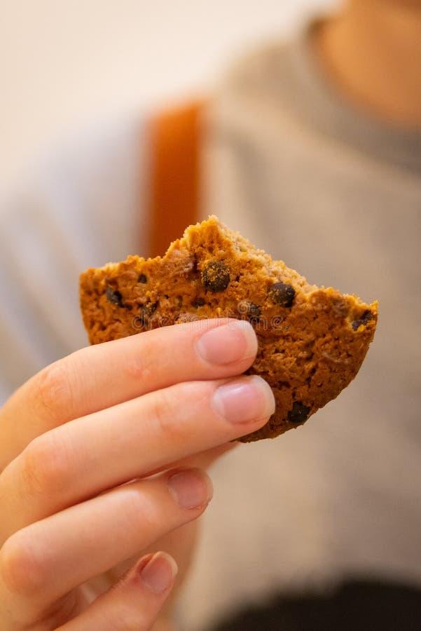 A cookie da aveia com chocolate remenda na mão da mulher fotos de stock royalty free