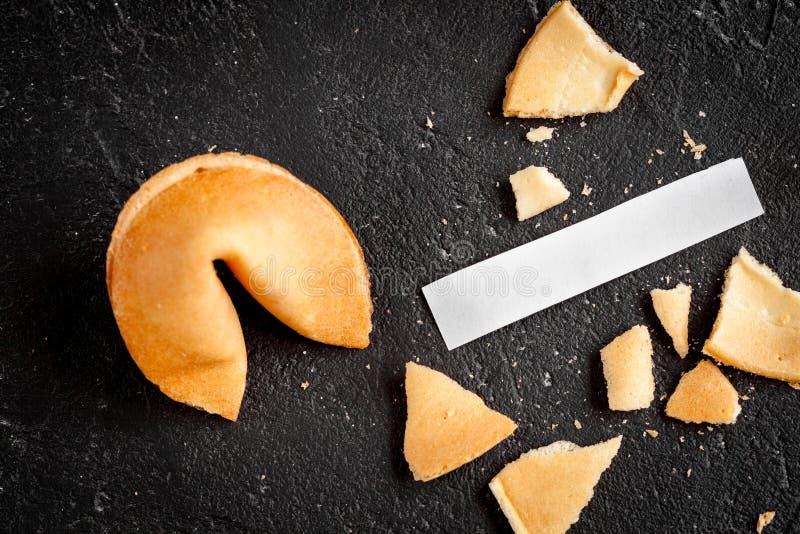 Cookie de fortuna chinesa com previsão na opinião superior do fundo escuro fotos de stock royalty free