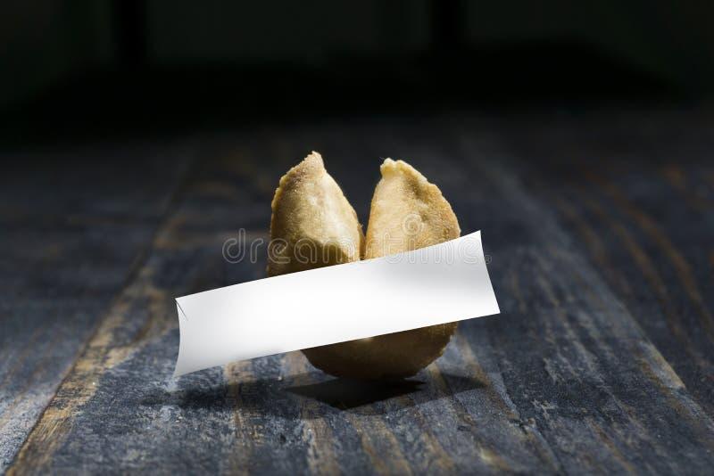 Cookie de fortuna na tabela de madeira com uma folha vazia do papel da esperança foto de stock