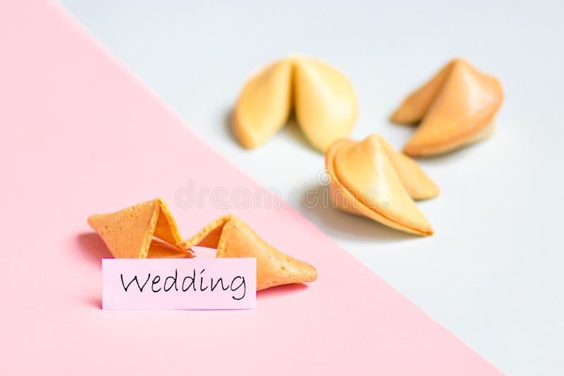 cookie de fortuna no rosa e no fundo azul, cores pastel, previsão do casamento fotografia de stock