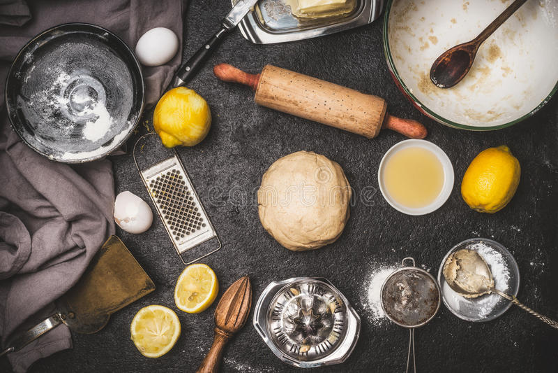 A cookie do limão ou a massa do bolo com cozimento de ingredientes e cozem ferramentas no fundo rústico escuro, vista superior imagens de stock