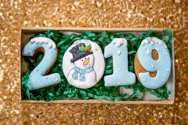 Cookie in the form of a numbers 2019 in carton box on golden background. Holiday sweets. New Year`s and Christmas theme. Festive stock photos
