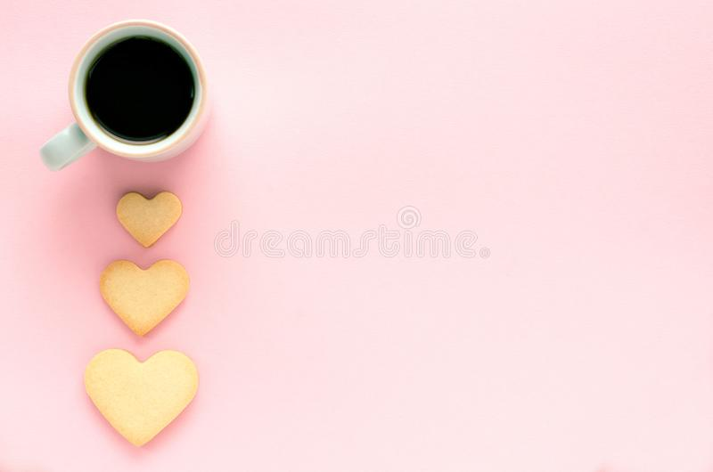 Cookie hearts and cup of coffee on pink background. Top view. stock images