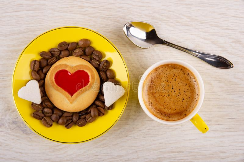 Cookie with jam heart, coffee beans, sugar in saucer, cup with espresso, spoon on table. Top view. Cookie with red jam heart, coffee beans, pieces of sugar in royalty free stock photo