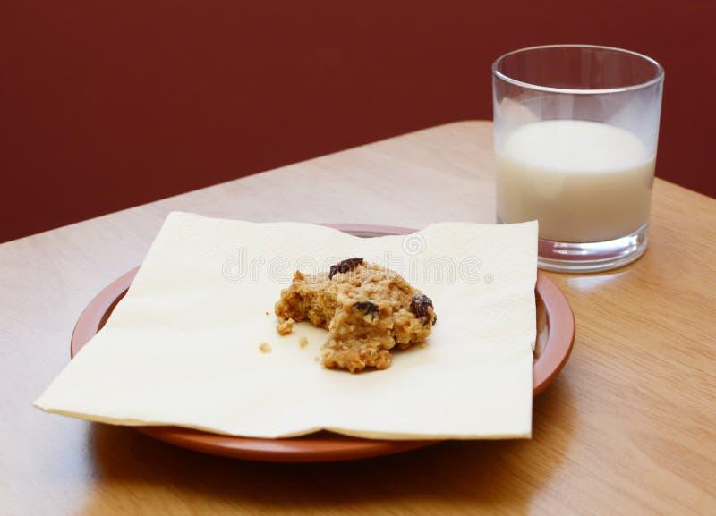 cookie Metade-comida com um meio vidro bebido do leite fotografia de stock