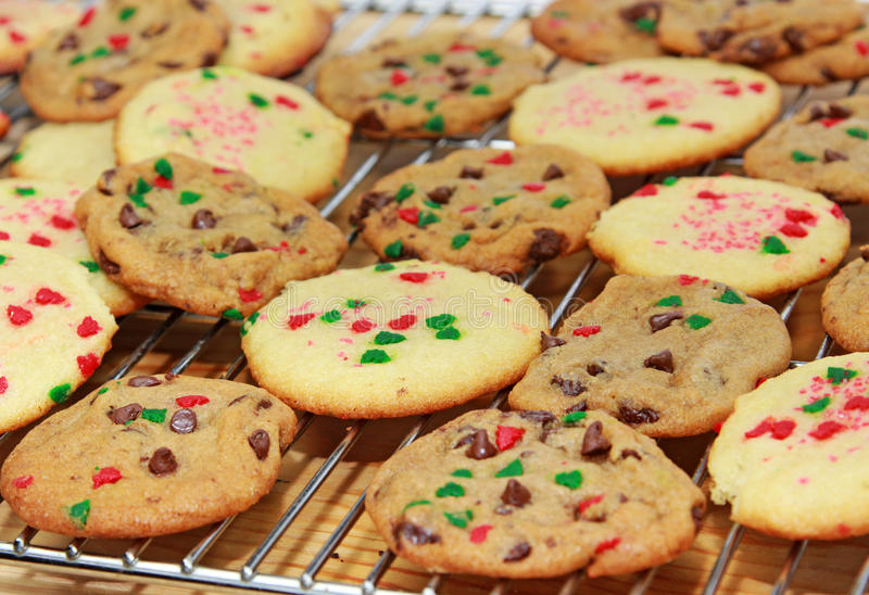 Cookies. Freshly home baked festive sugar and chocolate chip cookies decorated with green and red Christmas sprinkling cooling on a stainless steel rack royalty free stock images