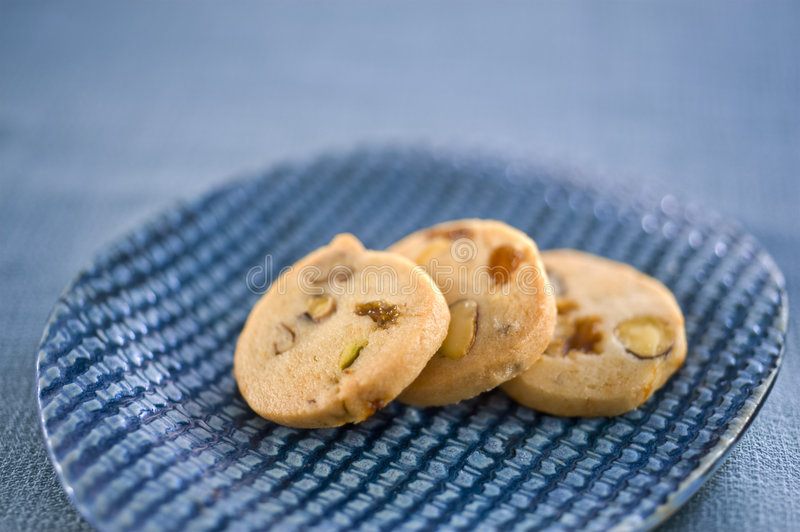Cookies. Three homemade cookies on a blue ceramic plate royalty free stock photography