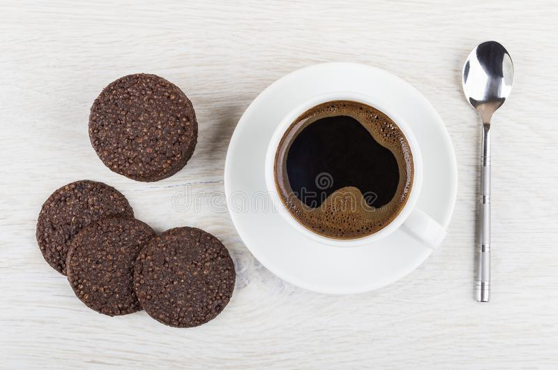 Cookies with airy rice, chocolate, coffee, spoon on light table. Cookies with airy rice and chocolate, black coffee in cup on saucer, spoon on light wooden table stock photo