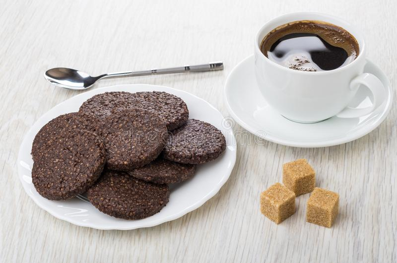 Cookies with airy rice, chocolate in plate, spoon, sugar, coffee. Cookies with airy rice and chocolate in white plate, spoon, sugar cubes, coffee in cup on royalty free stock photos