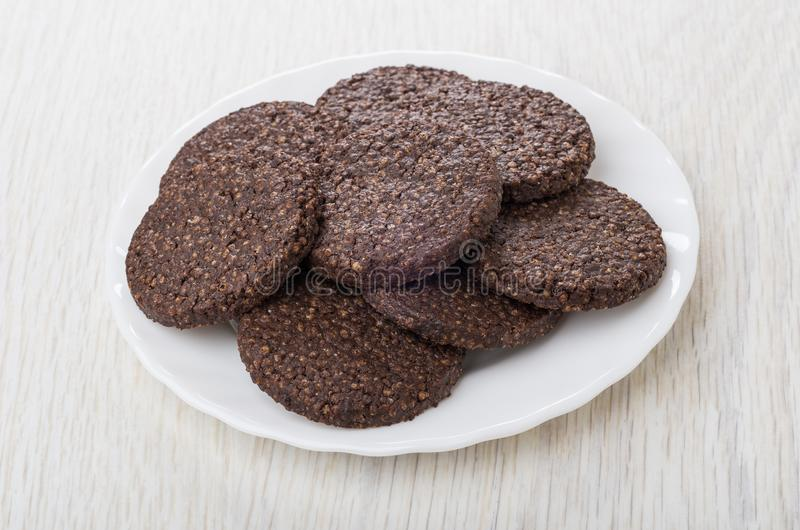 Cookies with airy rice and chocolate in white plate. On wooden table stock photography