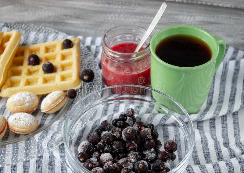 Cookies and berries on a bowl, tea in a green cup. Close-up stock image