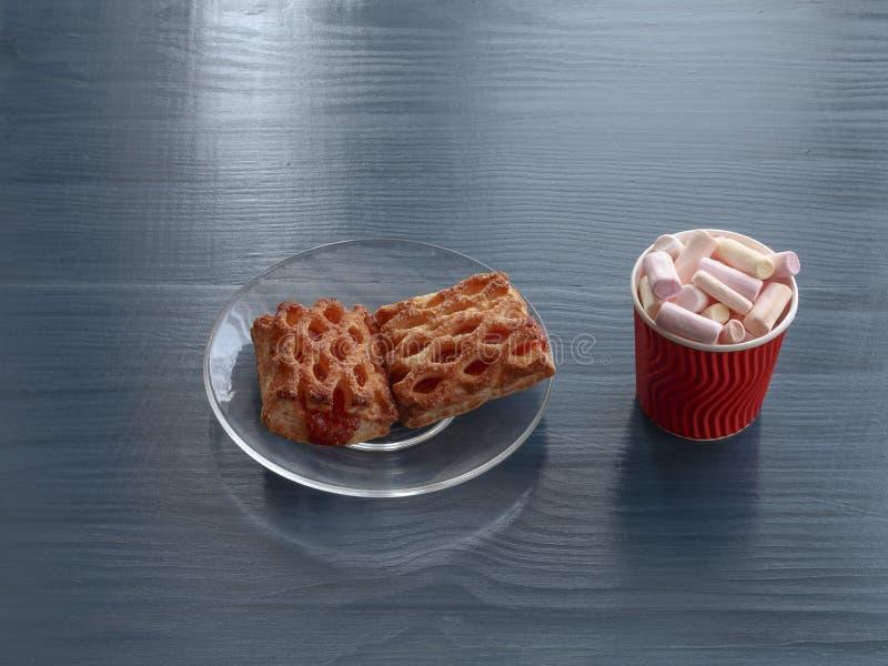 Cookies caseiros com doce em uma placa de vidro transparente e em marshmallows no copo vermelho em uma tabela de madeira imagem de stock