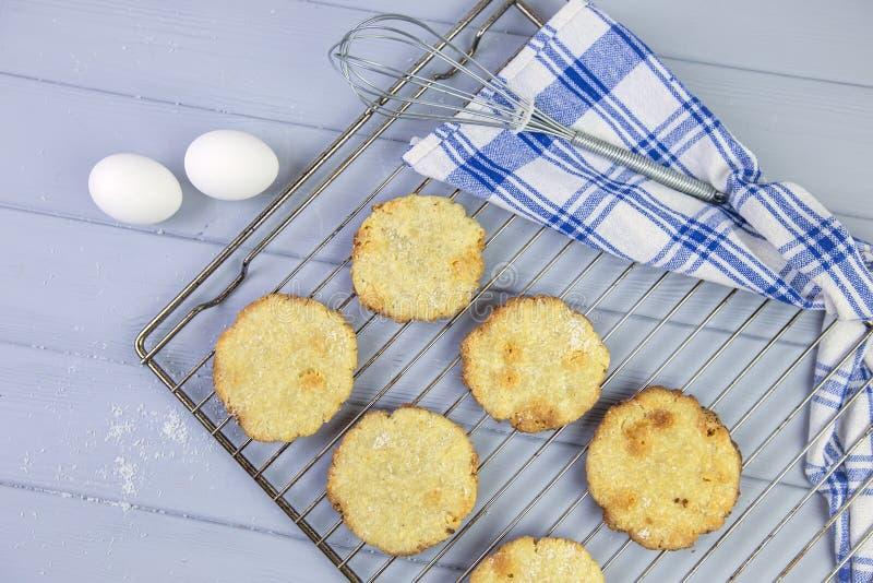 Cookies caseiros do coco em uma cremalheira de fio, apenas do forno, em um fundo cinzento de madeira, em torno dos ovos e das toa foto de stock royalty free