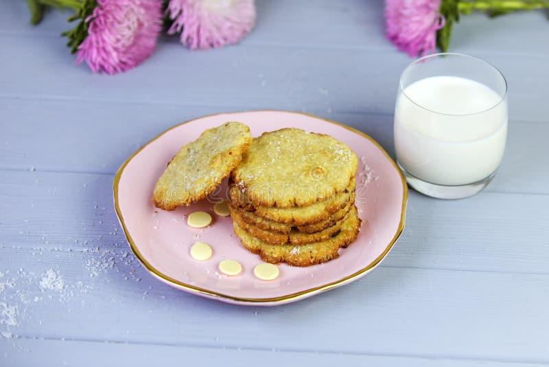 Cookies caseiros do coco na placa cor-de-rosa, apenas do forno, em um fundo cinzento de madeira, com vidro do leite e das flores imagem de stock