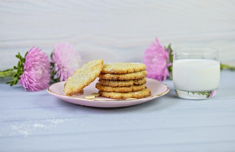 Cookies caseiros do coco na placa cor-de-rosa, apenas do forno, em um fundo cinzento de madeira, com vidro do leite e das flores foto de stock royalty free
