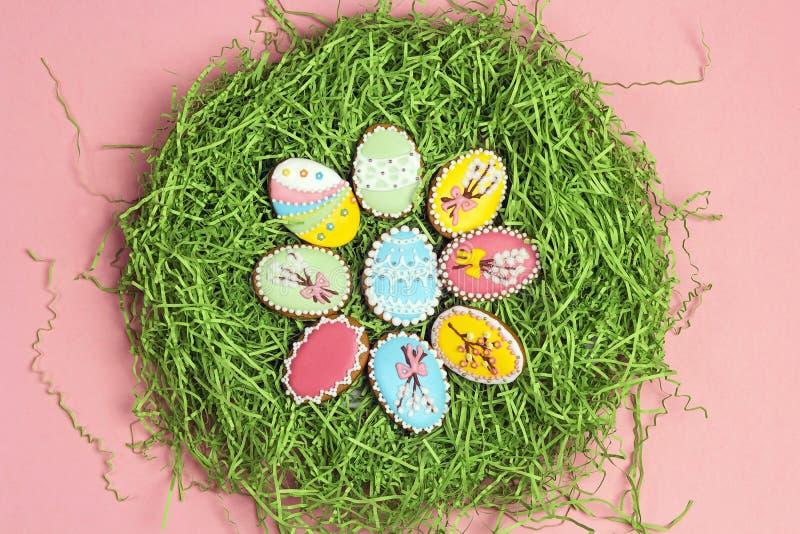 Cookies caseiros do pão-de-espécie na forma dos ovos da páscoa em um ninho verde fotos de stock royalty free