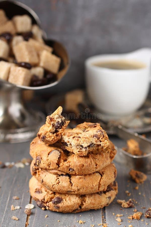 Cookies caseiros frescas dos pedaços de chocolate com o copo do café no fundo de madeira velho imagem de stock