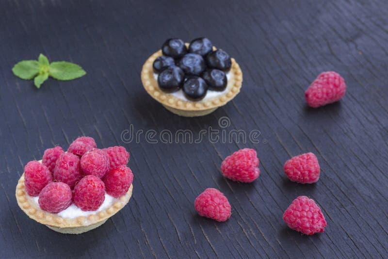 cookies Cesta-dadas forma com framboesas e mirtilos Fundo preto fotografia de stock