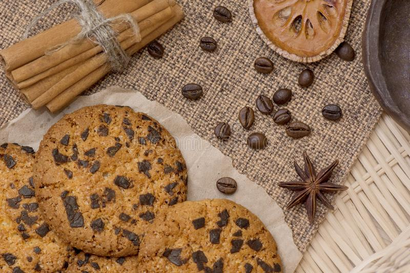 Cookies with chocolate, cinnamon, grain coffee, tubby and a clay cup on a straw tray stock images