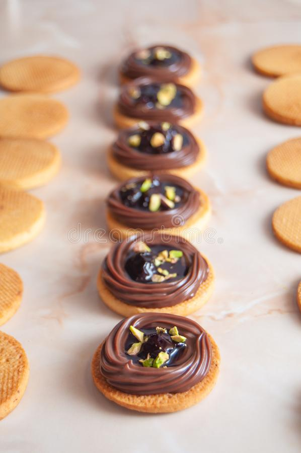 Cookies with chocolate cream, cherry and pistachio royalty free stock image