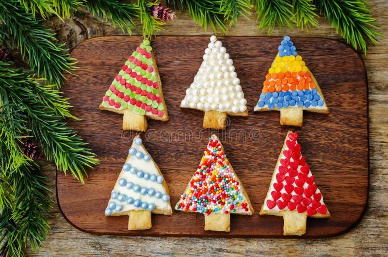 Cookies coloridas da árvore de Natal em um fundo de madeira escuro imagem de stock