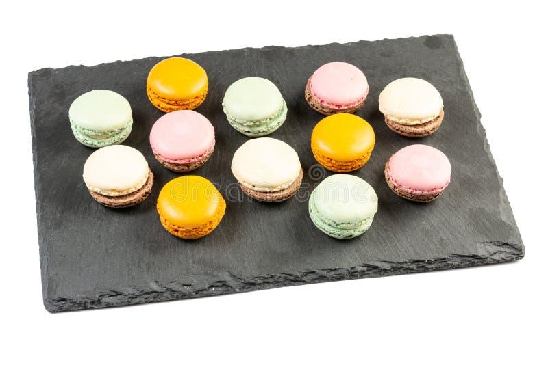 Cookies coloridas de Macarons na bandeja de pedra preta imagem de stock