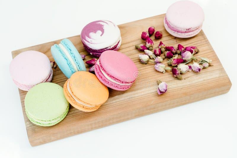 Cookies coloridas deliciosas francesas dos macarons e rosas pequenas na mesa de madeira Fundo branco imagens de stock royalty free