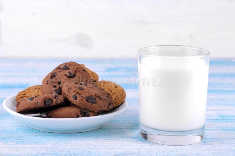 Cookies com chocolate em uma placa e em um leite em um vidro em um fundo de madeira azul baking yummy imagem de stock