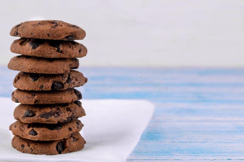Cookies com o chocolate dobrado em uma pilha em um guardanapo branco em uma tabela de madeira azul coza yummy Espaço para o texto fotografia de stock royalty free