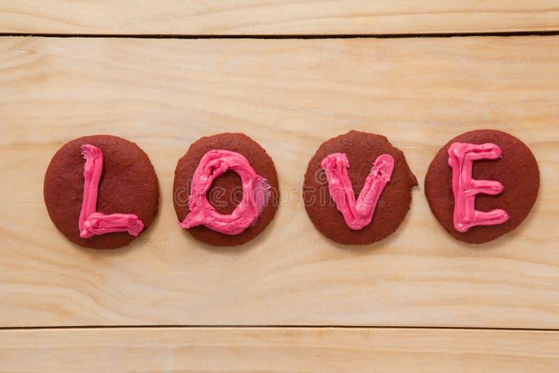Cookies congeladas com amor de indicação de creme cor-de-rosa fotografia de stock