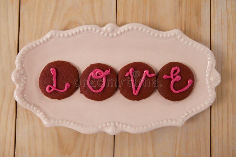 Cookies congeladas com amor de indicação de creme cor-de-rosa imagem de stock