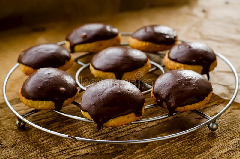 Cookies covered with dark chocolate glaze. Homemade cookies covered with dark chocolate glaze on wooden background. Selective focus stock images